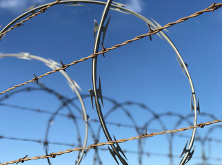 Barbed and Razor Wire Atop a Fence