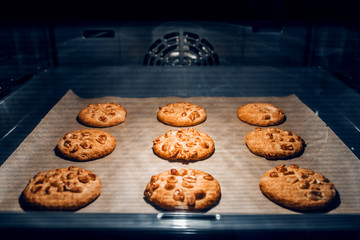 Round homemade cookies on a baking sheet in the oven