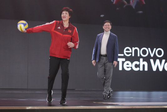 Chinese women's volleyball team coach Lang Ping throws a ball to delegates next to Lenovo Chairman and CEO Yang Yuanqing at Lenovo Tech World in Beijing