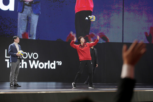 Chinese women's volleyball team coach Lang Ping sends a ball to delegates next to Lenovo Chairman and CEO Yang Yuanqing at Lenovo Tech World in Beijing