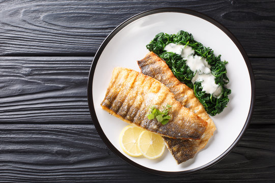 Serving fried sea bass fillet with spinach and lemon closeup on a plate. Horizontal top view
