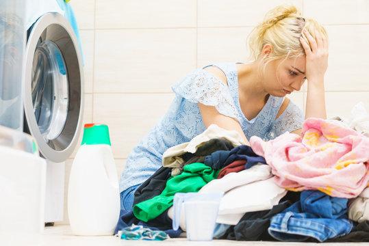 Unhappy woman having a lot of laundry