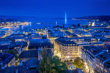 Türaufkleber Dunkelblau Aerial view of Geneva City center and Jet d'eau by night on World Diabetes Day. This photo was taken shortly after sunset, at the blue hour, from the top of the tower of St. Peter's Cathedral.