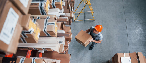Top view of male worker in warehouse with box in hands Wall mural