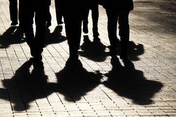 Silhouettes and shadows of people on the city street. Crowd walking down on sidewalk, concept of strangers, crime, society, gang or population