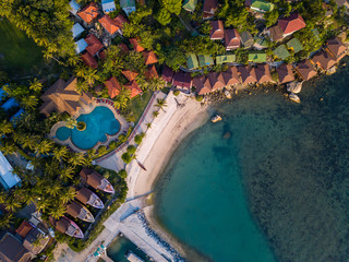 Aerial: Above  beachfront resort with sea view on beautiful tropical island koh Phangan, Haad Rin...