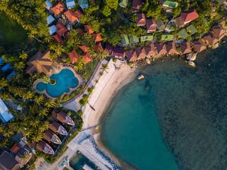 Aerial: Above  beachfront resort with sea view on beautiful tropical island koh Phangan, Haad Rin area