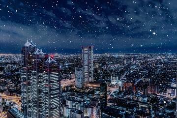 雪が降る新宿の夜景イメージ(合成)