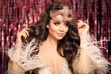 Foto op Canvas Carnaval Beautiful brunette with Healthy wavy hair. Fashion Beauty Girl with carnival mask Isolated on golden bokeh Christmas lights Background. Glamour Makeup. Gold Jewelry copy space. Hairstyle.