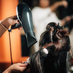 Hairdresser Curling Woman's Hair.