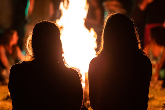 silhouette of two girls sitting in the front of the fire as they watching night musical show, seen from behind during dark night campfire, blurred background