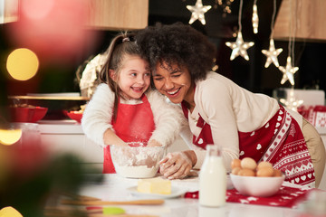 Girl and her mum baking cookies for Christmas