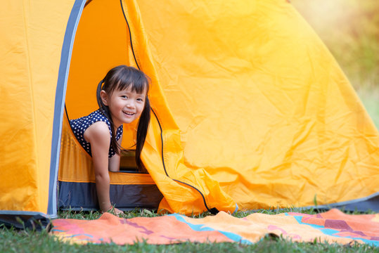 Little Asian girl smile and looking at camera playing with her tent on campsite, happy girl sitting inside yellow tent at park