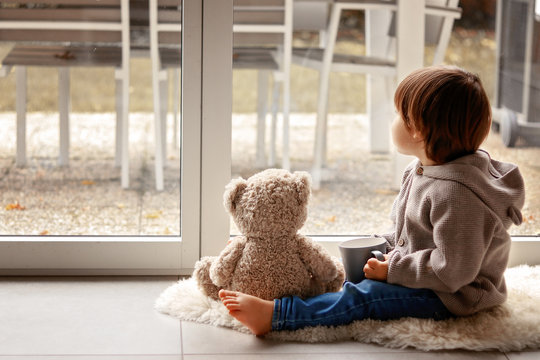 Cute little toddler boy sitting at window with cup of warm tea with his soft teddy bear toy looking out thoughtfully at chilly autumn weather. Cozy home. Fall melancholy concept. Seasonal mood