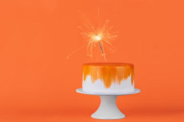 Colorful birthday cake with sparkling on stand. Copy space concept. Poster idea.