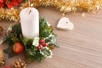 Candle on table with Christmas floral arrangement and heart top