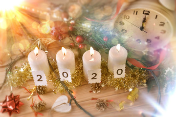 Candles and clock on table celebrating new year 2020 top