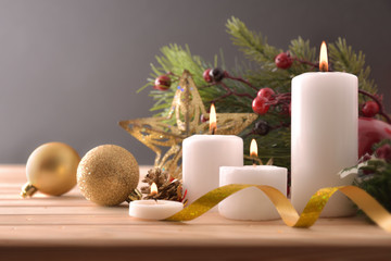 Four burning candles on wooden table with Christmas decoration front