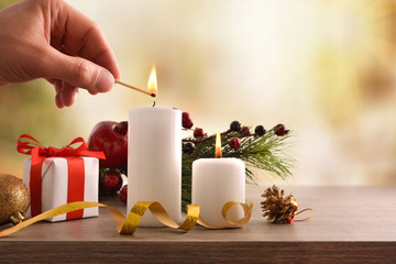 Hand lighting candles on decorated table at Christmas