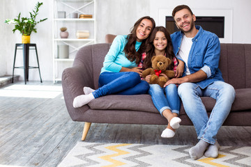 Our family portrait. Full-length family picture of mom, dad and their cute daughter with a teddy bear, smiling and hugging on the couch in the cozy home atmosphere.