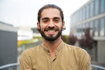 Handsome happy bearded man. Portrait of cheerful young man standing outdoors and smiling at camera. Emotion concept