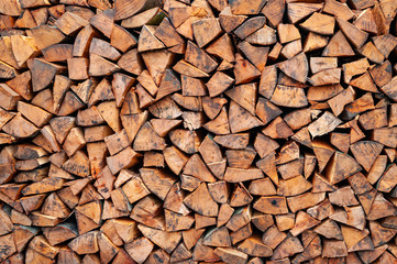 Stack of firewood. A lot of firewood is piled up by the wall.