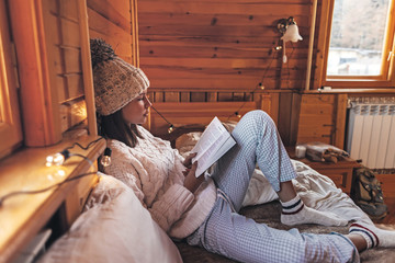 Girl relaxing and reading book in cozy log cabin in winter