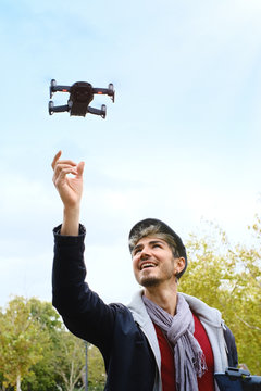 Young Man With Remote Control Landing Drone In His Hands