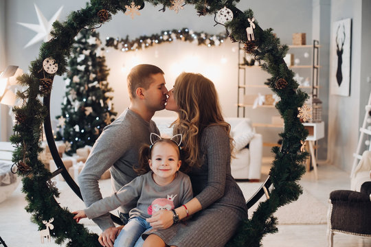 Full length stock photo of three family members daughter, mother and father snuggling on decorated Christmas swing in circled shape with fir branches.