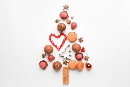 Christmas tree shape made of tasty treats on white background