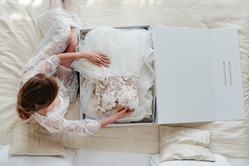 Portrait of beautiful bride in dressing gown holding luxury wedding dress on bed, copy space. Wedding concept. Top view, above