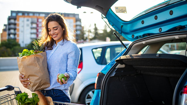 Woman after shopping in a mall or shopping centre and driving home now with her car outdoor. Beautiful young woman shopping in a grocery store/supermarket, putting the groceries into her car