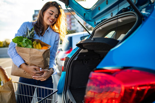 Woman putting her shooping bags into car at shopping mall parking lot. She has done some light shopping,mainly food. Young happy beautiful woman shifts the purchase from shopping cart in the trunk