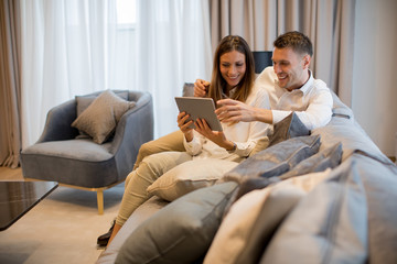 Lovely young couple with digital tablet in the room