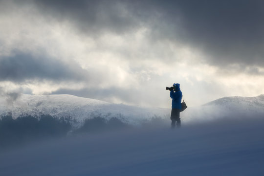 Photographer with the photocamera stands on the lawn covered with snow. Stormy sky with the sun rays. High mountains. Winter foggy scenery. Location place the Carpathian, Ukraine, Europe.