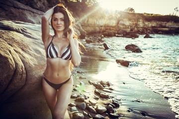 Beautiful brunette girl in bikini posing on a beach