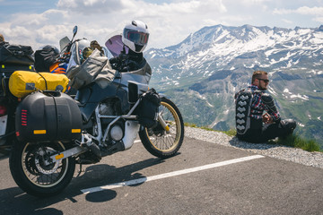 A motorcycle traveler sitting on the edge of the earth and looking into the distance. top of the mountain, Grossglockner pass, biker dressed in a protective jacket armor. Austria, motorbike with bags Fototapete