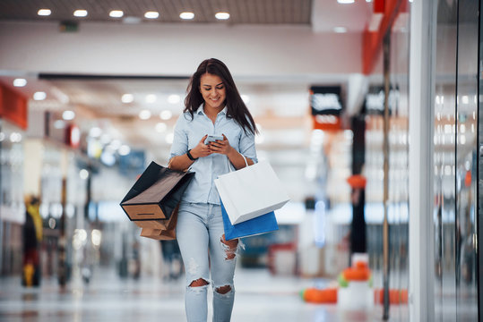 Brunette woman in the supermarket with many of packages and phone in hands have shopping day