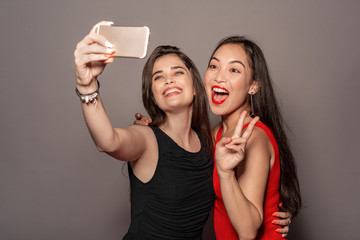 Freestyle. Young girls in dress standing hugging isolated on gray taking selfie on smartphone posing showing salute gesture smiling excited