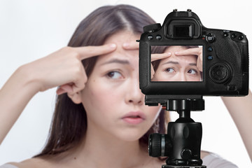 Asian woman squeezing spot on forehead on camera, social media concept