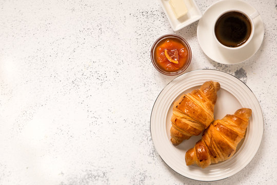 breakfast with croissants. fresh crispy croissants and coffee on a light .background, top view..