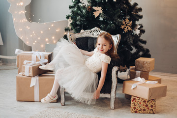 Full length stock photo of beautiful little girl in festive white dress sitting relaxed in armchair. There are many presents wrapped in decorative paper. Pretty girl against decorated Christmas tree.