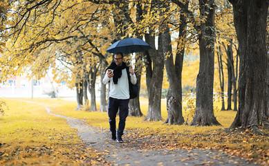 Foto op Canvas Meloen A young man in glasses walks in the park with an umbrella during the rain.