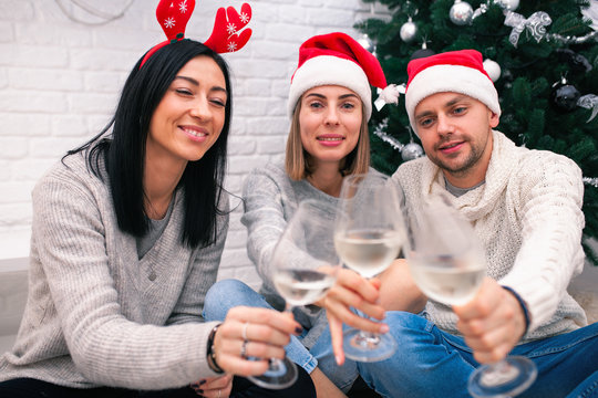 Happy friends celebrating New Year in home interior in Christmas hats sitting near a Christmas tree with glasses of wine