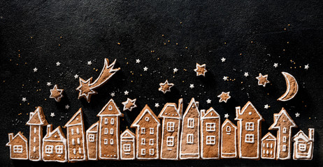 Christmas background, gingerbread  cookies houses and gingerbread stars  on a black  background....