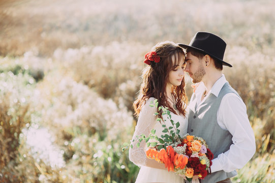 Happy beautiful wedding couple bride and groom at wedding day outdoors . Happy marriage couple outdoors on nature, soft sunny lights