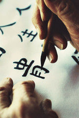Art Photo of a Chinese calligrapher painting a character.