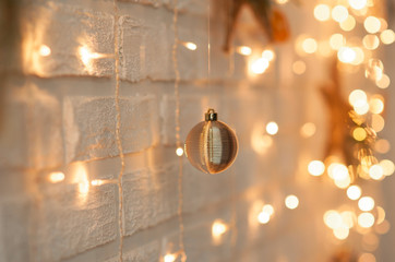 Beautiful Christmas decoration of white brick wall with garlands and Christmas tree toys.