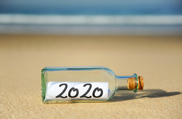 2020 Summer vacation concept. Message in a bottle on the sand of beach