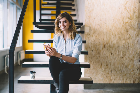 Portrait of happy smiling female employee looking at camera while sitting with mobile phone at office stairs, positive woman in formal wear using cellular application for online purchase and shopping